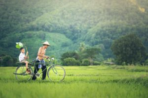 Cambodian Child and Father on Bike in green Nature